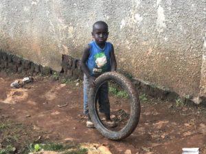 Junge mit Reifen in Kazo Kawempe Uganda